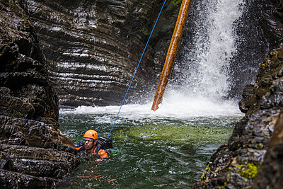 Man swims to safety after rappelling down waterfall. - p1166m2138013 by Cavan Images