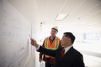 Contractor and architect reviewing blueprints on wall - p1192m1403529 by Hero Images