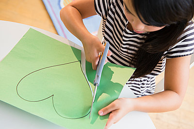 Filipino girl cutting heart shape out of paper - p555m1415576 by JGI/Jamie Grill