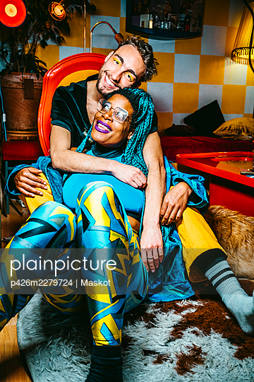 Portrait of smiling young man hugging female hipster friend while sitting in living room - p426m2279724 by Maskot
