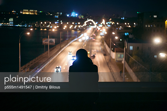 Silhouette of person watching traffic from overpass at night - p555m1491547 by Dmitriy Bilous