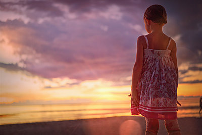Pensive girl watching tranquil sunset in dramatic sky over ocean  - p1023m1446541 by Tom Merton