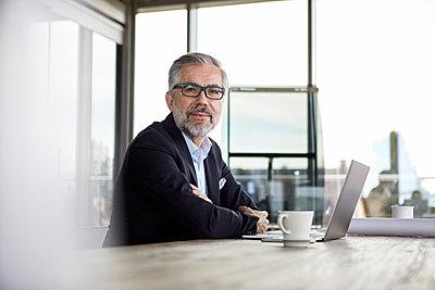 Portrait of confident businessman with laptop at desk in office - p300m2012954 von Rainer Berg