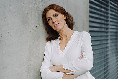 Portait of a pensive businesswoman leaning against a concrete wall - p300m2155361 by Joseffson