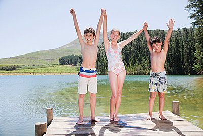 Kids standing with arms raised on dock - p64115336f by Robert Daly