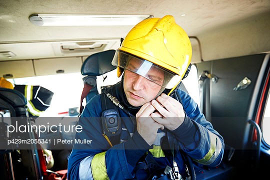 Fireman putting on helmet in fire engine - p429m2058341 by Peter Muller