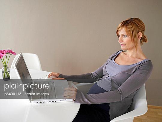 Schwangere Frau arbeitet am Laptop  - p6430113 von senior images