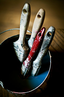A collection of paintbrushes in liquid in a brush pail.  - p1100m1158321 by Mint Images