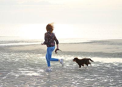 Frau rennt mit Hundewelpen am Strand - p1124m1223964 von Willing-Holtz
