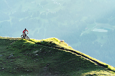 Mountainbiker on a way in Grisons, Switzerland - p300m2167079 by Hannah Bichay