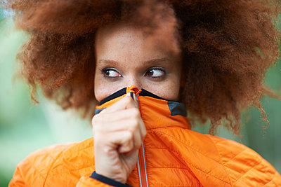 Portrait of woman covering mouth with coat looking away - p429m1197955 by Peter Muller