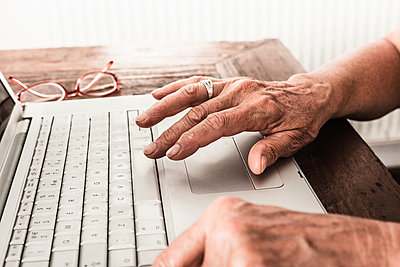 Close up of older mans hands on laptop - p429m659697f by Dan Brownsword