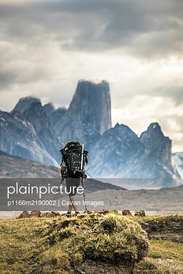 Backpacker hikes toward Mount Asgard in Akshayak Pass, Baffin Island - p1166m2190002 by Cavan Images