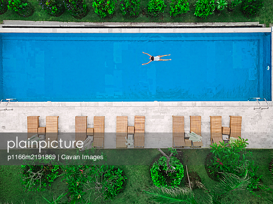 Aerial view of attractive woman floating over water at resort - p1166m2191869 by Cavan Images