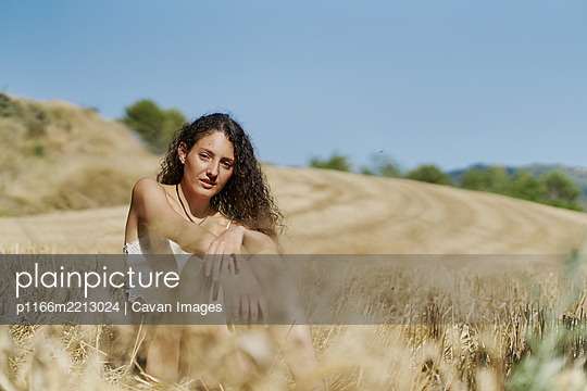 Curly haired young woman in a wheat field - p1166m2213024 by Cavan Images