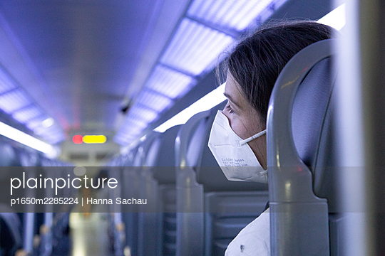 Junge Frau mit FFP2 Maske im Zug - p1650m2285224 von Hanna Sachau