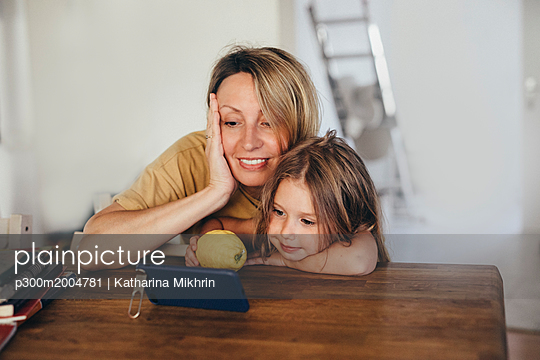 Mother and little daughter using smartphone at new home - p300m2004781 von Katharina Mikhrin