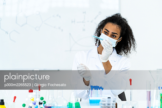 Female researcher analyzing liquid in test tube at laboratory during COVID-19 - p300m2265523 by Giorgio Fochesato