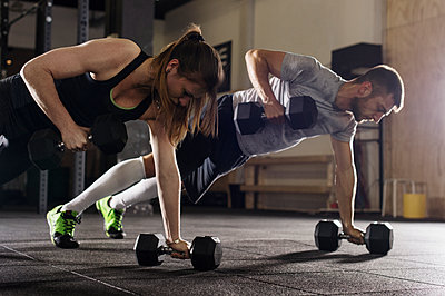 Determined male and female athletes doing push-ups while exercising with dumbbells in gym - p1166m1154104 by Cavan Images