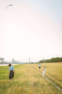 Germany, Cologne, family flying kite in a field - p300m1101047f by Matthias Drobeck