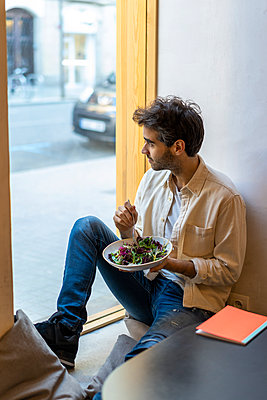 Man eating a salad sitting at the window in a restaurant looking out - p300m2113905 by VITTA GALLERY
