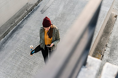 Stylish young woman with skateboard and cell phone on parking deck - p300m2121927 by Uwe Umstätter