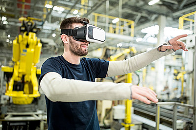 Man wearing VR glasses in modern factory - p300m2246020 by Westend61