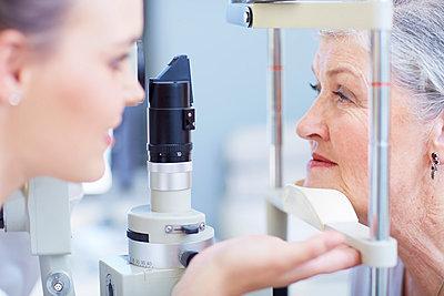 Eye doctor examining senior woman's vision - p300m975593f by zerocreatives