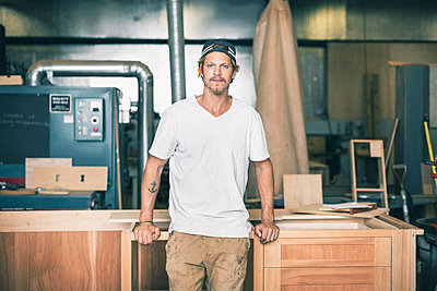 Portrait of confident carpenter leaning on cabinet in workshop - p426m1062603f by Maskot