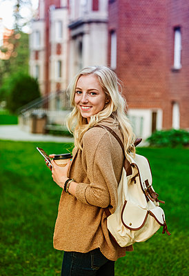 A beautiful young woman with long blond hair holding a coffee cup and texting on her smart phone while walking in a university campus stops to pose for the camera; Edmonton, Alberta, Canada - p442m2004142 by LJM Photo