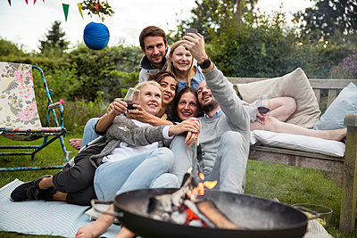 Friends taking a selfie on garden party - p788m1165287 by Lisa Krechting