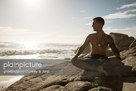 Man practises meditation on the beach in the sunshine - p1640m2261017 by Holly & John