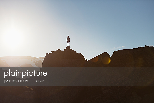 Hiker on top of mountain - p312m2119060 by Johner