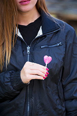 Young woman holding heart-shaped lolli-pop - p1149m2142132 by Yvonne Röder