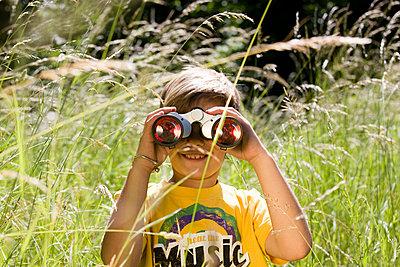 Boy looking through binoculars - p7610027 by Adeleida