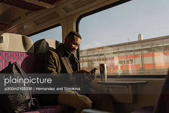 Stylish man using smartphone inside a train - p300m2155336 by Hernandez and Sorokina