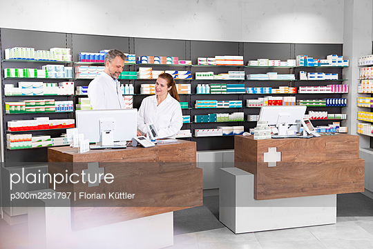 Male and female pharmacists working at pharmacy checkout - p300m2251797 by Florian Küttler