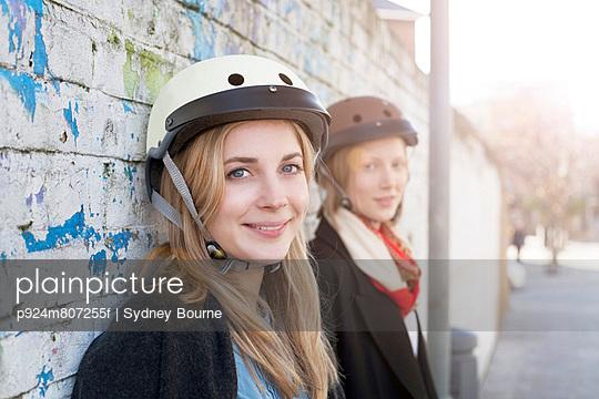 Women wearing bicycle helmets - p924m807255f by Sydney Bourne