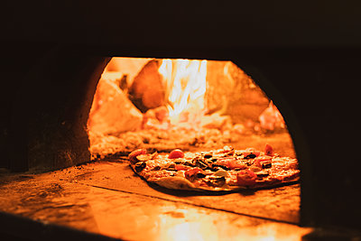 Close up of pizza in a wood-fired oven in a restaurant. - p1100m2220408 by Mint Images