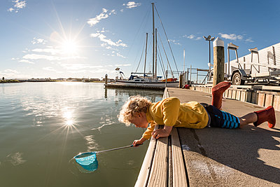 Curly haired young boy with net on sunny day - p1166m2137183 by Cavan Images