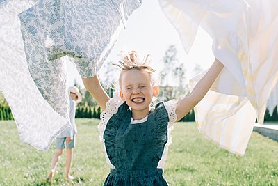 girl running through the washing on a line in the garden having fun - p1166m2201728 by Cavan Images