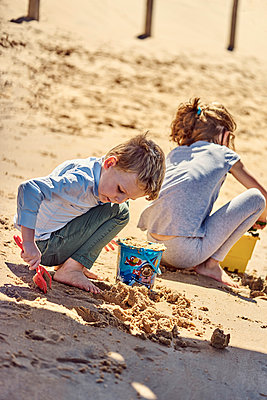 Brother and sister playing with sand on the beach - p300m2005683 by Benjamin Egerland