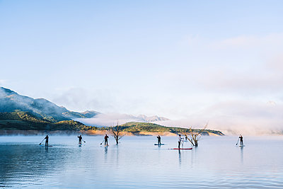 Group of people stand up paddle surfing on a lake - p300m2170541 by Daniel González