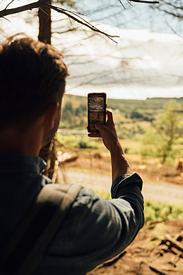 Mid adult man photographing landscape while smart phone in forest - p300m2213917 by Boy photography