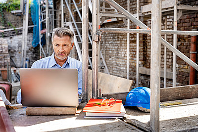 Mature engineer working on laptop while sitting at construction site - p300m2256443 by Peter Scholl