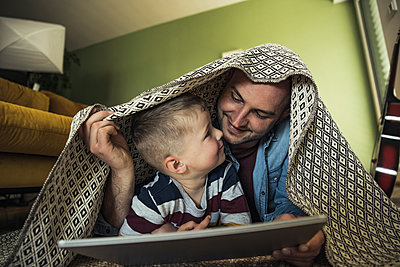 Smiling father and son looking at each other while under blanket in living room at home - p300m2286862 by Uwe Umstätter