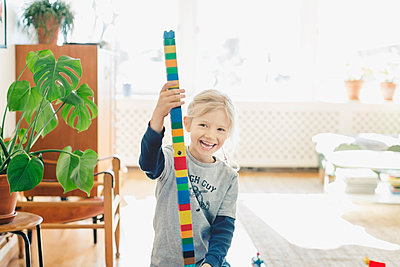 Happy girl holding tower made of toy blocks at home - p426m1062372f by Maskot