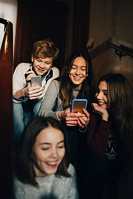 Happy teenage boy with female friends using mobile phone while sitting on steps - p426m1555927 by Maskot