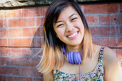 Portrait of smiling Chinese woman with headphones - p555m1301976 by Take A Pix Media