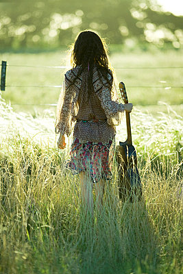 Young hippie woman holding guitar - p6241731f by Laurence Mouton